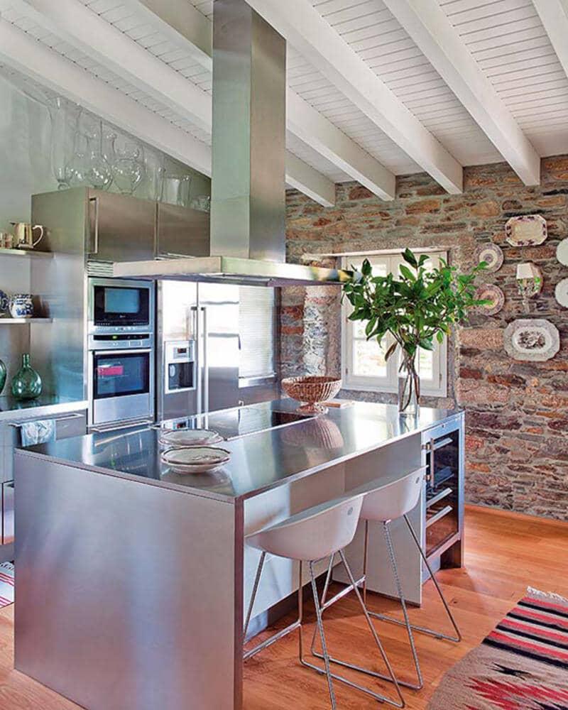 cocina estilo industrial con isla y extractor en acero inoxidable y piedra