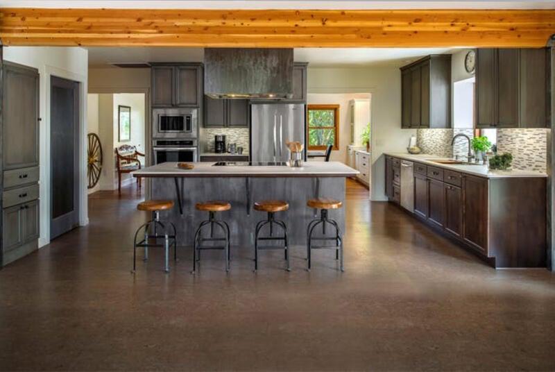 cocina estilo industrial con piso de carpeta de cemento y viga de madera