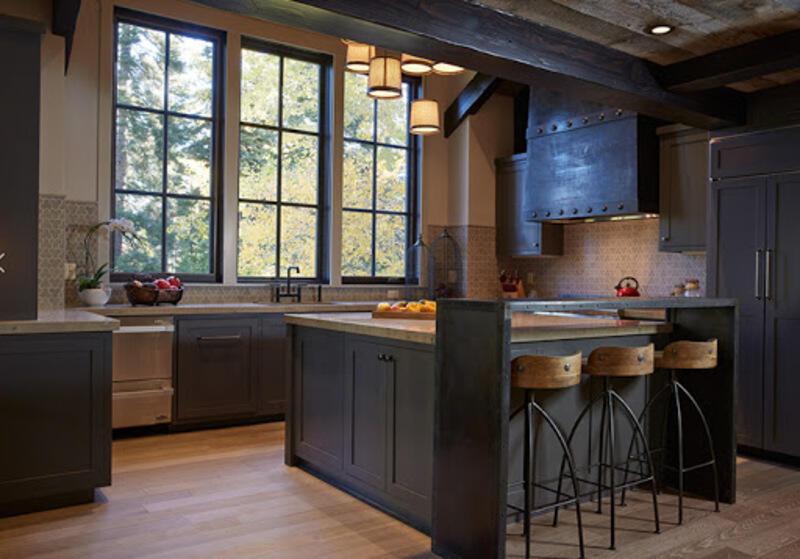 cocina estilo industrial con ventanas, isla y taburetes